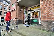 Nederland, Berg en Dal, 20-3-2020   Deze zelfstandige winkelier met een doe het zelfzaak heeft in de voordeur van zijn winkel een balie gemaakt waar klanten kunnen aangeven wat ze willen waarna hij het zelf uit de winkel pakt. Er mag maar een klant tegelijk aan de balie staan . Inventieve voorzorgsmaatregel tegen het coronavirus .Foto: Flip Franssen