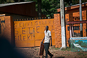 """A street vendor who sells phone cards walks in front of a metal gate which was vandalized by Séléka rebels who took over Bangui, the capital city, back in March 2013. Seven months after the coup, there was a relative peace in the capital city and the suburbs; however, violence in the countryside, in towns such as Bossangoa and Bouar continue to threaten the security of the country resulting in killings, over 200,000 IDPs, torture, rape, and forced disappearances. Séléka, meaning """"union"""" or """"allegiance"""" in Sango language, propelled the current CAR interim President Michel Djotodia into power Séléka forces are still causing instability in the country, waging battles with pro-Bozizé supporters known as Anti-Balaka to this date. The insecurity drove the country into total chaos in almost every sector, as its citizens merely try to survive from day to day."""