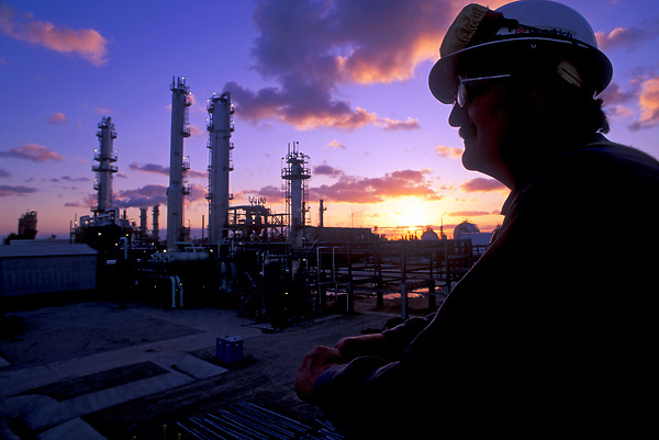Man working at petrochemical facility overlooks a refinery and colorful sunset in Houston, Texas.