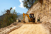 A Mahindra backhoe loader and construction team working on the road to Raniswara, on the 3rd of March 2020 in Ghairung, Gorkha, Nepal.  This team of road workers have increased the width of this mountain road to improve safety, this type of work happen regularly and traffic waits for it to be passable again.