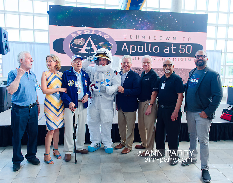 Garden City, New York, U.S. July 20, 2019. L-R, ALAN CONTESSA, Nassau County Executive LAURA CURRAN, ERNEST FINAMORE, (wearing space suit) TOM RUHLE, Suffolk County Executive STEVE BELLONE, Cradle of Aviation Museum President ANDY PARTON, MIKE LISA, and NYS Senator KEVIN THOMAS pose in front of stage at the Moon Fest Apollo at 50 Countdown Celebration at Cradle of Aviation Museum in Long Island, held during the same time Apollo 11 Lunar Module landed on the Moon 50 years ago.