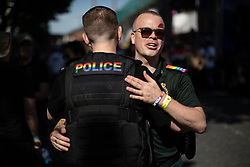 © Licensed to London News Pictures . 24/08/2019. Manchester, UK. Policeman and Paramedic hug . The 2019 Manchester Gay Pride parade through the city centre , with a Space and Science Fiction theme . Manchester's Gay Pride festival , which is the largest of its type in Europe , celebrates LGBTQ+ life . Photo credit: Joel Goodman/LNP