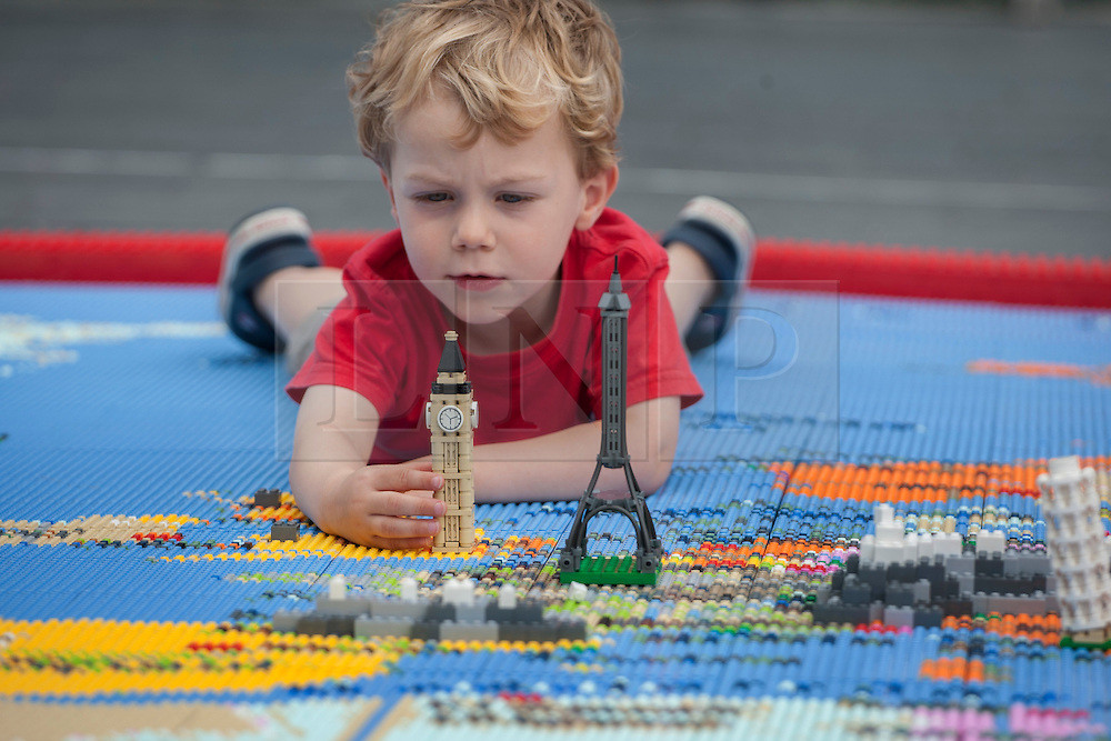 © licensed to London News Pictures. London, UK 13/08/2012. A child playing with Lego replicas of landmarks on a giant map of the world, measuring 12 by 5 metres, made from over a million Lego bricks by members of public and designed by Duncan Titmarsh for the Festival of the World at Southbank Centre. Photo credit: Tolga Akmen/LNP