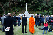 A Buddhist Monk watches a Christian Priest talking during  the Remembrance Sunday ceremony at the Hodogaya, Commonwealth War Graves Cemetery in Hodogaya, Yokohama, Kanagawa, Japan. Sunday November 12th 2017. The Hodagaya Cemetery holds the remains of more than 1500 servicemen and women, from the Commonwealth but also from Holland and the United States, who died as prisoners of war or during the Allied occupation of Japan. Each year officials from the British and Commonwealth embassies, the British Legion and the British Chamber of Commerce honour the dead at a ceremony in this beautiful cemetery.
