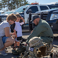 Amanda Kolar and her son Ezra Kolar learn about all of the equipment the Gallup Police Department uses from officer Lionel Desiderio at the 6th Annual Preparedness and Public Safety Day, Saturday at the Rio West Mall.