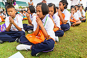 "23 APRIL 2013 - BANGKOK, THAILAND:  Thai students pray during the opening ceremony to mark Bangkok as the World Book Capital City 2013. UNESCO awarded Bangkok the title. Bangkok is the 13th city to assume the title of ""World Book Capital"", taking over from Yerevan, Armenia. Bangkok Governor Suhumbhand Paribatra announced plans that the Bangkok Metropolitan Administration (BMA) intends to encourage reading among Thais. The BMA runs 37 public libraries in the city and has modernised 14 of them. It plans to build 10 more public libraries every year. Port Harcourt, Nigeria will be the next World Book Capital in 2014. .PHOTO BY JACK KURTZ"