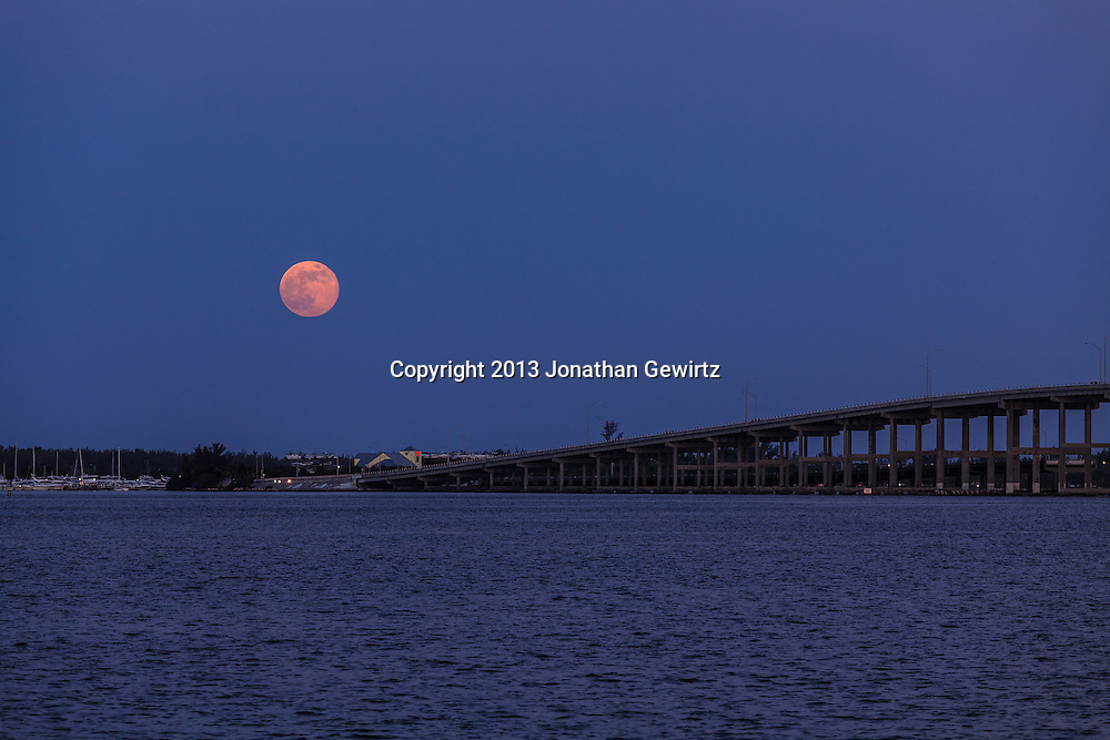 The full moon rises over Virginia Key and the William Powell Bridge in Biscayne Bay at Miami. WATERMARKS WILL NOT APPEAR ON PRINTS OR LICENSED IMAGES.