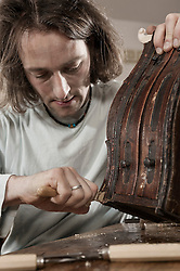 Carpenter repairing an antique bone box at workshop, Bavaria, Germany