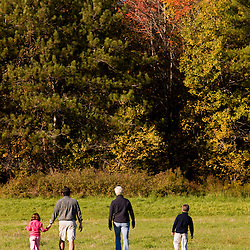 A young family walks in a hay field at the Clark Farm in Windham, Maine.