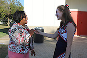 "A Lamar High School cheerleader hands out an early voting sticker outside the Metropolitan Multi-Services Center on West Gray after Lamar and HSPVA students performed a ""Thriller"" flash mob for those waiting to vote.<br />