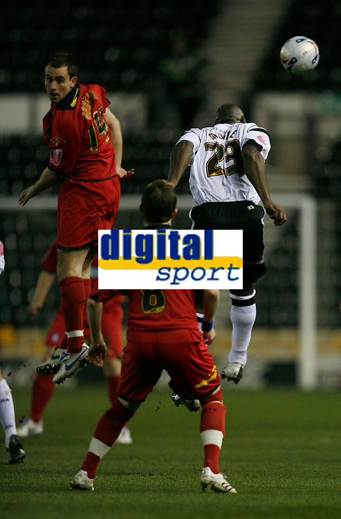 Darren Moore of Derby (right) beats Richard Garcia of Colchester (left) in an aerial challange. Jamie Cureton looks on.