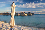 Sun umbrella and overwater bungalows at the Bora Bora Nui Resort & Spa. Previously a Starwood Luxury Collection property, the Bora Bora Nui is now operated by Hilton. Bora Bora is one of the Leeward Islands in the Society Islands archipelago of French Polynesia.