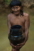 Huaorani Indian woman - Dabe Baiwa using clay pot for carrying water from the river. Gabaro Community. Yasuni National Park.<br /> Amazon rainforest, ECUADOR.  South America<br /> The Huaorani clay pots have a unique shape compared with any of the other indian tribes in Ecuador.<br /> She has the typical stretched ear lobes common amoung the Huaorani. They often wear balsa ear plugs.<br /> This Indian tribe were basically uncontacted until 1956 when missionaries from the Summer Institute of Linguistics made contact with them. However there are still some groups from the tribe that remain uncontacted.  They are known as the Tagaeri. Traditionally these Indians were very hostile and killed many people who tried to enter into their territory. Their territory is in the Yasuni National Park which is now also being exploited for oil.