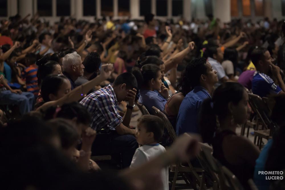 """Juan Martinez, de 17 años,  reza en el Ministerio de la Cosecha, durante la """"Gran Cruzada"""" religiosa. Juan no había podido asistir a la iglesia desde que fue deportado, pues su vida está amenazada de muerte. (Prometeo Lucero)"""
