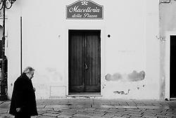 Reportage sviluppato ad Alessano (LE). Viene presa in considerazione fotograficamente, la gente che popola il paese nei suoi bar, piazze, strade, giardini pubblici. Ed, insieme a questa, i particolari caratterizzanti il luogo...donna cammina in un vicolo del centro storico