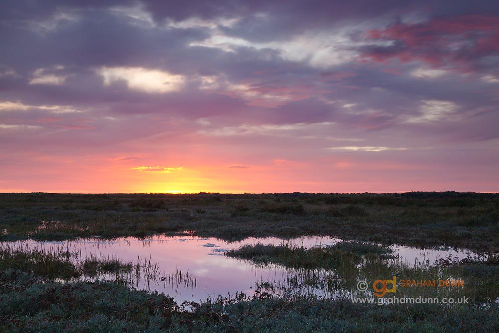 Dusk reflections at high tide, Holme next the sea salt marsh. North Norfolk, East Anglia.
