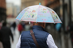© Licensed to London News Pictures. 22/08/2016. Leeds, UK. A man shelters under a rather girly umbrella on a rainy and windy day in Leeds, West Yorkshire. Forecaster are predicting a heatwave this week, but it has started with rain, wind and no sunshine. Photo credit : Ian Hinchliffe/LNP