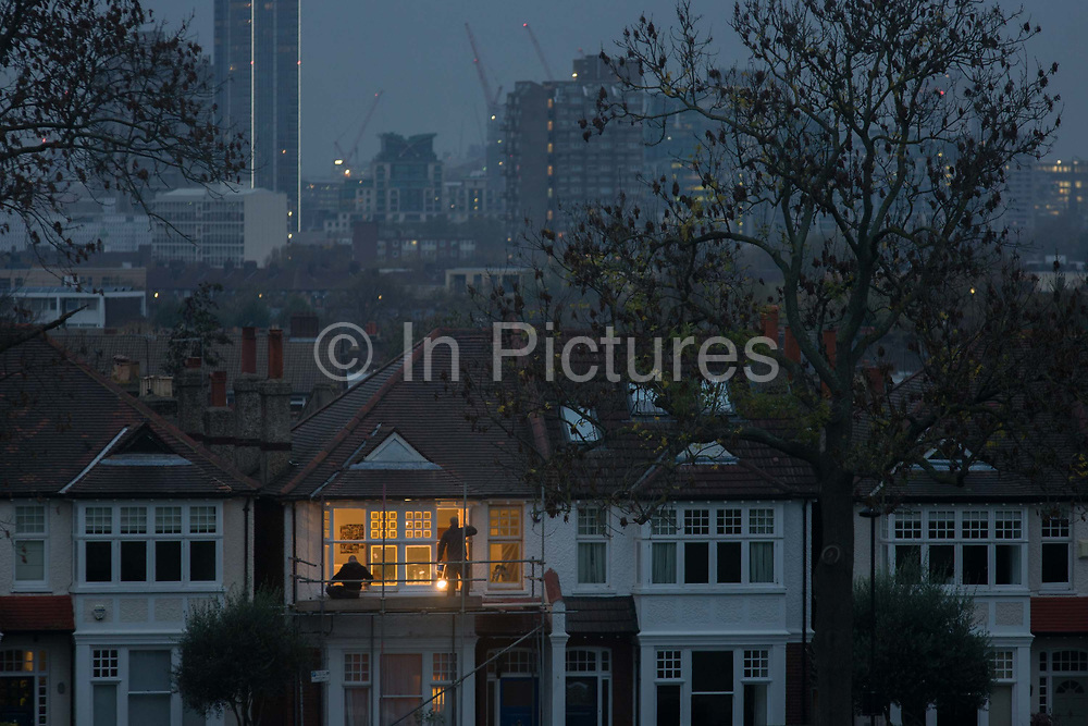 Two decorators work on scaffolding on the first floor of an Edwardian period home in south London. Warm light from inside the house contrasts with blue winter light at dusk a few miles south of parliament in Westminster. Other homes are in darkness. It is late one evening in central London, in a suburb known as Herne Hill, SE24 in the borough of Lambeth. We see across the metropolis from quiet and expensive period homes, whose owners would typically be white middle-class, across to the blocks of flats (apartments) in the Loughborough Estate, a far rougher location for street gangs and high crime rates.