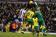 Norwich keeper John Ruddy punches clear from WBA's Shane Long. Barclays Premier league, West Bromwich Albion v Norwich city at the Hawthorns in West Bromwich, England on Sat 7th Dec 2013. pic by Andrew Orchard, Andrew Orchard sports photography.