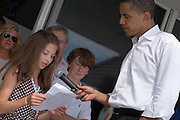 CHATHAM, Mass. - August 8, 2007: U.S. Democratic presidential candidate Sen. Barack Obama, D-Ill., takes a moment to answer a question from Sara Kate, daughter of famed singer, actor and song writer Harry Conick, Jr. and fashion model mother Jill Goodacre during a fundraiser in Chatham, Mass.