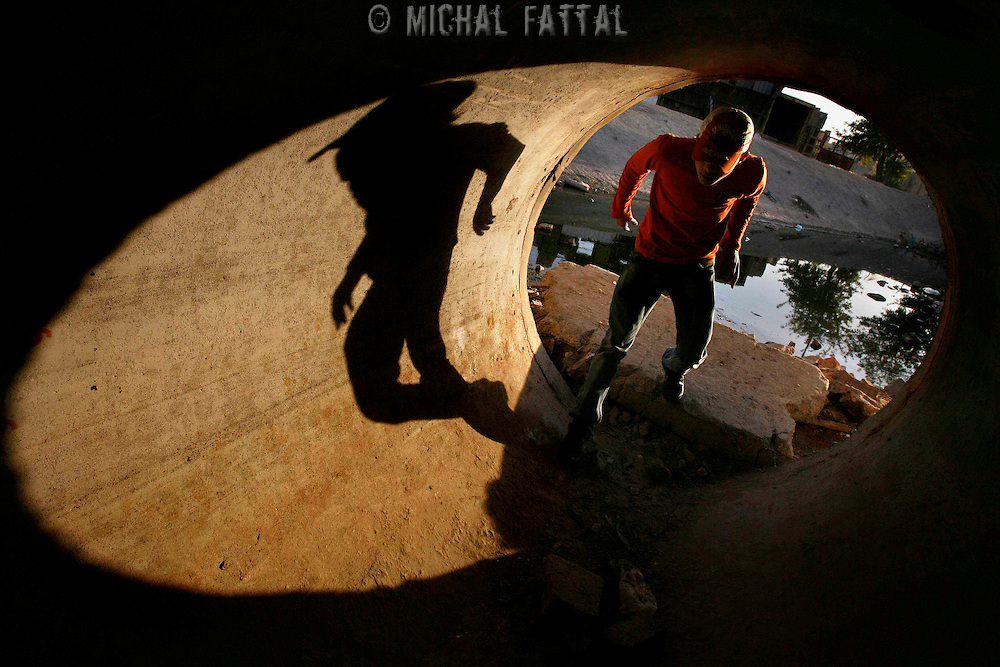 A Palestinian man passes through a sewage pipe under the separation wall at the West Bank village of A-Ram on the outskirts of Jerusalem, November 2007.