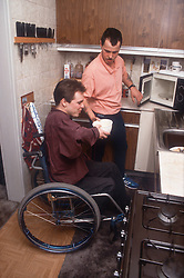 Man with disability; who is wheelchair user; preparing meal in kitchen with carer,