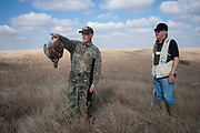 Experienced hunters Timmy Stein with a grouse and Byron Grubb out on the North Dakota prairie grasslands shooting upland game birds near Minot, North Dakota, United States. Byron has been shooting for most of his life and puts considerable efforts into his hunting, efforts which reward him with wild game meats, none of which is wasted.
