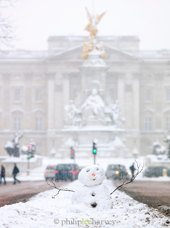 A snowman and Buckingham Palace on the Mall in London, UK