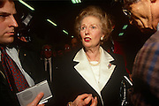 Surrounded by reporters, ex-British Prime Minister Margaret Thatcher leaving the 1992 Tory party conference on 9th October 1992 in Blackpool, England. Two years after her colleagues deposed her, forcing her to resign from her 11 year premiership she is still in favour by Conservatives who are proud to display her in public, before eventually shunning her policies and profile for their campaigns. Surrounded by supporters, the media, an aide on the left and in the red, her personal protection police officer. Thatcher has been lending her support to the election campaign of her replacement, John Major who went on to win and govern until his defeat in 1997 to Labour's Tony Blair.