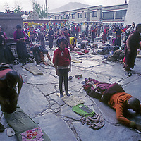 CHINA, TIBET, LHASA. Tibetan Buddhist devotees prostrate & pray in front of Jokhang Temple, holiest site in Tibet.