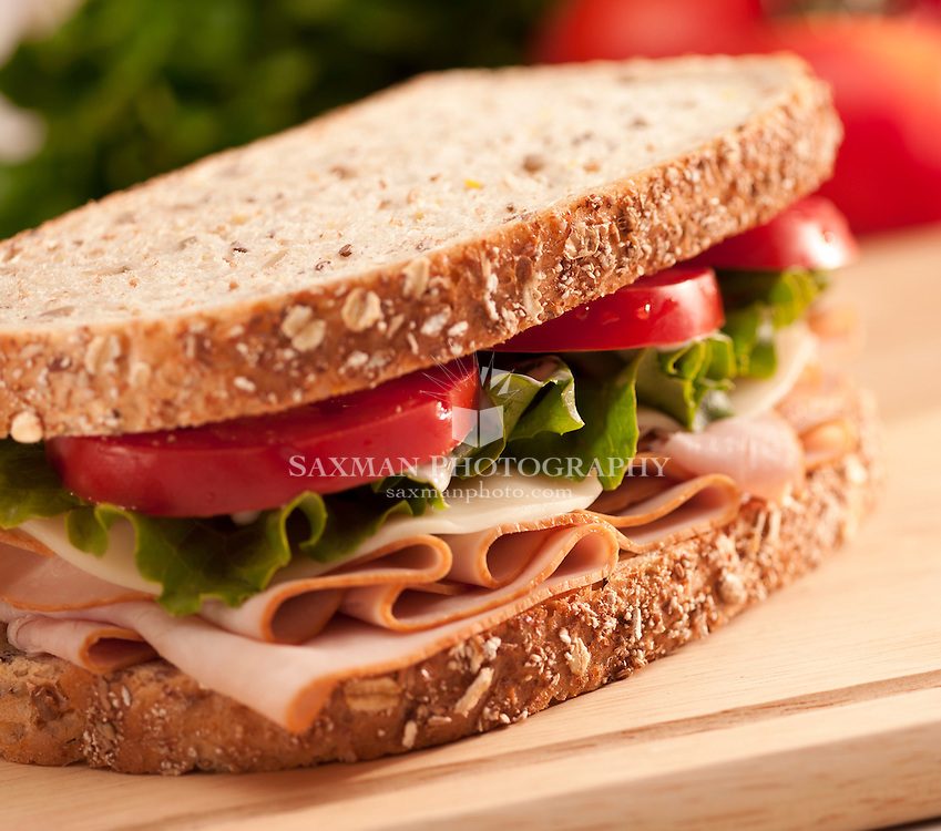 Turkey sandwich with lettuce and tomatoes on whole grain bread on a cutting board.