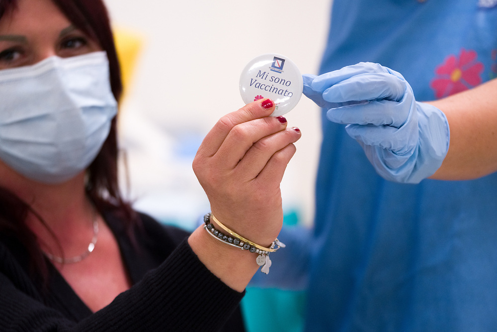 """A woman wearing a protective face mask against the spread of COVID-19 coronavirus holds a pin reading """"Mi sono vaccinato"""" (I got vaccinated) after received a dose of the Pfizer-BioNTech COVID-19 vaccine at Ospedale del Mare in Naples, southern Italy, on December 27, 2020. Today is started the vaccination campaign simultaneously throughout Europe."""