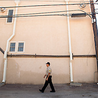 102313       Brian Leddy<br /> Wyatt King walks the alley between Coal and Aztec during a routine patrol Wednesday. The city recently hired Red Rock Security and Patrol after several incidents of theft and public intoxication.