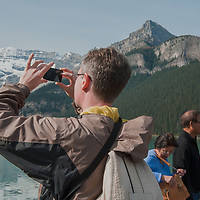 Tourists photograph at Lake Louise in Banff National Park, Alberta, Canada.