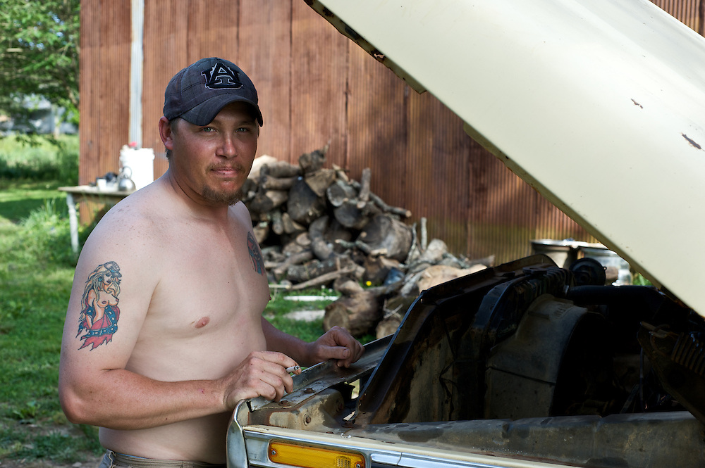 A man stands by his pickup truck in the small town of Gaylesville, Alabama