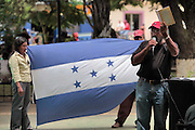 A protester waves a copy of the Honduran constitution in a protest of the ousting of Honduran president Manuel Zelaya a year after he was flown into exile by the military. There are still pockets of Hondurans who want the president returned to power, while most claim that things are better off since the coup d'etat. Honduras is considered the third poorest country in the Western Hemisphere (Haiti, Nicaragua). With over 50% of the population living below the poverty line and 28% unemployed, Hondurans frequently turn to illegal immigration as a solution to their desperate situation. The Department of Homeland Security has noted an 95% increase in illegal immigrants coming from Honduras between 2000 and 2009, the largest increase of any country.