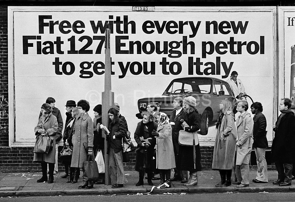 Queue waiting for bus in North Kensington in front of Fiat advertising poster. The Fiat 127 was one of the first of the modern superminis, and won praise for its utilisation of space  as well as its road-holding. The 127 was an instant success, winning the European Car of the Year award for 1972, and quickly became one of the best-selling cars in Europe for several years. Coming and Going is a project commissioned by the Museum of London for photographer Barry Lewis in 1976 to document the transport system as it is used by passengers and commuters using public transport by trains, tubes and buses in London, UK.