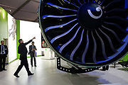 A visitor to the General Electric (GE) exhibition stand at Britain's Farnborough Air Show, points to a feature on a massive, GE90-115B turbofan jet engine. Powering Boeing 777 airliners with up to 115,000 Pounds of thrust, this is a state-of-the-art engine that entered service in April 2004 with Air France. Its giant blades are lit with blue stage lighting to make it look iconic and imposing, dominating this picture of technology and innovation. Such mechanical excellence attached to the world's aircraft are helping to make them quieter and more energy and fuel efficient at a time when oil prices are making air travel an expensive mode of transport.