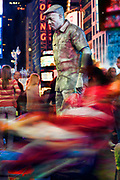 A mime appears to not respond to distraction in the middle of Times Square.