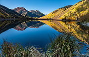 Red Mountain, Hayden Mountain, and golden aspens reflect in Crystal Lake on a sunny morning in Uncompahgre National Forest, San Juan Mountains, south of Ouray, Colorado, USA. This image was stitched from multiple overlapping photos.