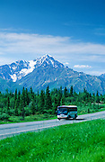 Alaska. A Grayline Holland America, HAL, tour bus travels the Glenn Highway with the Chugach Mts in the background.