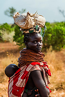 Nyangatom tribe woman carrying her baby on her back, Omo Valley, Ethiopia.