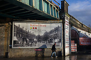 Property estate agent's billboard showing old street scene under railway bridge in Herne Hill, South London SE24. The south London business Burnet Ware has handled the sale and lettings of houses and properties since 1882 in the 19th century. The picture on the billboard shows us the junction in Herne Hill of Half Moon Lane with Victorian shops lining the street on both sides. The area grew as a result of the railways and the rail bridge overhead still handles trains travelling from the southern suburbs into central London.