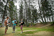 Thomas Nichini, left, practices a three-part version of Scotland the Brave alongside Logan Fraser and Aaron Sentell on the grassy lawn adjacent to the North Idaho College beach on Monday. The camp, which began in 1970, features around eighty pipers from throughout the Northeast and will feature two concerts on Tuesday and Thursday evening at NIC.
