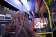 Girl listening to music on her headphones whilst travelling on the bus. London, UK.
