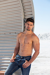 shirtless muscular man by a metal sun shelter