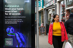 © Licensed to London News Pictures. 07/03/2020. London, UK. A woman walks past a Coronavirus public information campaign poster in London, which focuses on hand washing. Forty two more people have tested positive of the virus, taking the total to 206 in the UK. Photo credit: Dinendra Haria/LNP