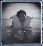 Portrait of a little girl who is swimming in sea waters. She wears a lifebelt for drowning prevention. Palawan island, Philippines, Asia