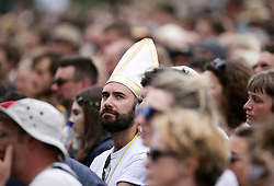 A festivalgoer wearing a Papal tiara-style hat watching Laura Marling performing on the Pyramid Stage at Glastonbury Festival, at Worthy Farm in Somerset.