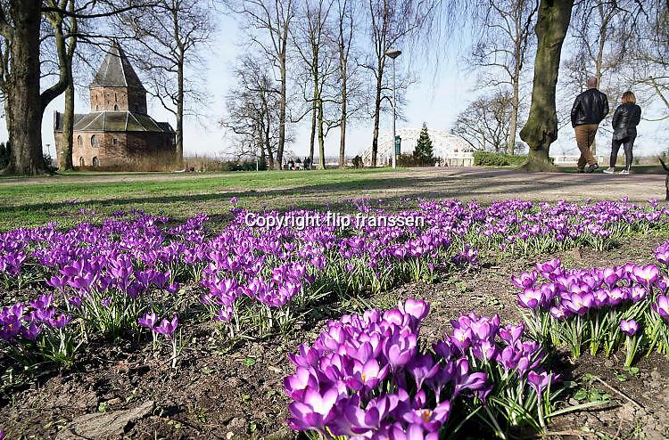 Nederland, Nijmegen, 12-3-2017Mensen genieten van de zon, en het uitzicht op de waal en de waalbrug vanaf het valkhof, valkhofpark . Het is een stadspark met de resten van de burcht, palz, van Karel de Grote . De Karolingische kapel deel uitmakend van de verdwenen palz . Krokussen staan in bloei .Foto: Flip Franssen